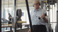 MS DS Senior man with dumbbells exercising in gym / Vancouver, British Columbia, Canada
