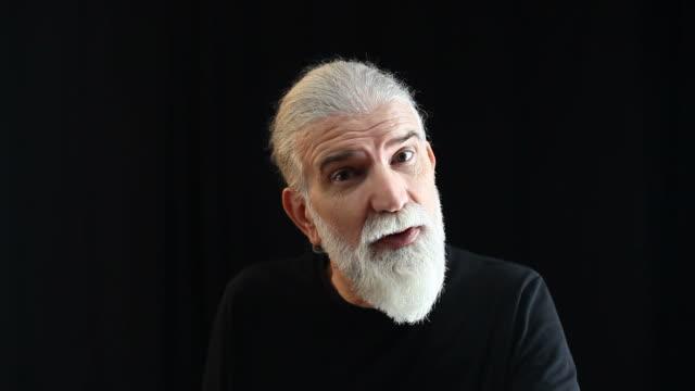 Senior man with gray hair and beard talking to camera