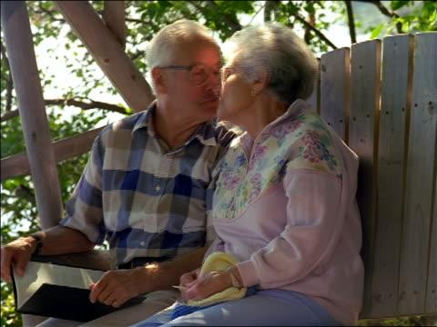 Senior man + woman sitting on porch swing looking at book, kissing + laughing