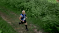 AERIAL Senior marathon participant running through forest