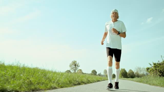 SLO MO TS Senior marathon runner running on a sunny day