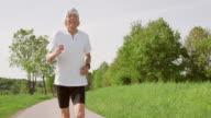 SLO MO TS Senior marathon runner running through nature
