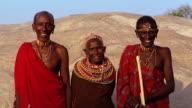 MS senior Masai tribeswoman standing between two tribesmen outdoors / Kenya