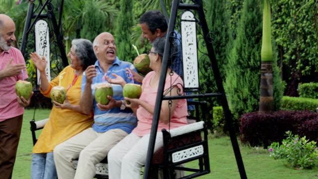 Senior men and senior women drinking coconut water in the park, Delhi, India