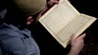 Senior muslim imam reading in dark