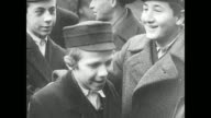 POLAND Senior Polish Jewish men in overcoats hats standing on sidewalk talking horse buggy BG MS Boys talking laughing together Jewish men standing...