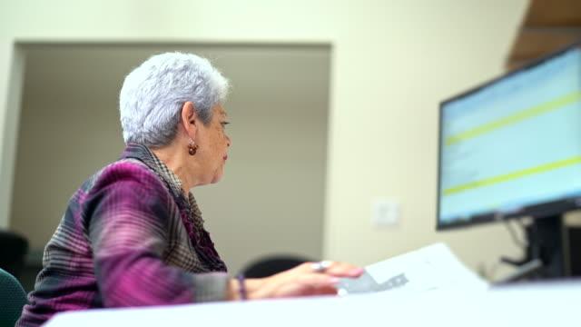 Senior silver-haired vrouw, ingenieur, het meten van de ruimte op de tekening van architecturaal project met curvimeter.