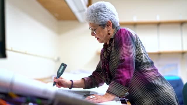 Senior silver-haired vrouw, ingenieur, met behulp van curvimeter wanneer ze werken met architecturaal project