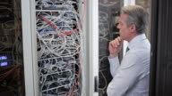 Senior technician contemplating about cable mess in server room