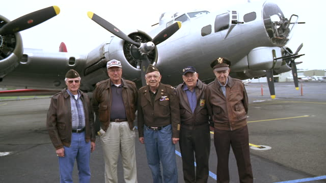 WS Senior veterans in military uniforms standing near B-17 Flying Fortress propeller airplane / Seattle, Washington, USA