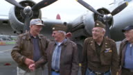 MS Senior veterans in military uniforms walking near B-17 Flying Fortress propeller airplane and shaking hands / Seattle, Washington, USA