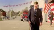 Senior war veteran walking down street after parade / California
