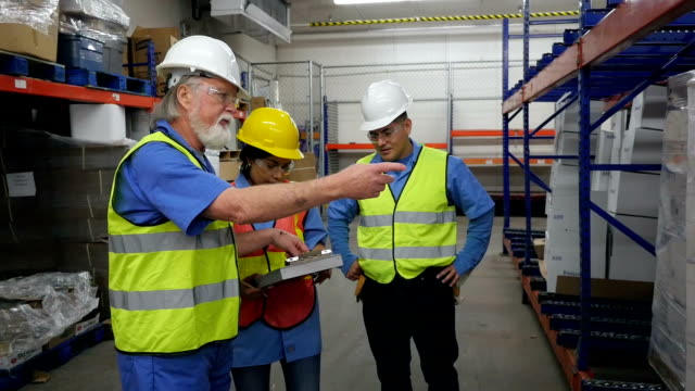 Senior warehouse manager explaining inventory to factory coworkers