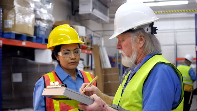 Senior warehouse manager training new female blue collar employee