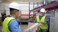Senior warehouse worker discussing distribution order with Hispanic coworker