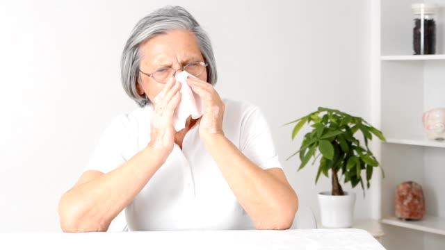 Senior woman blowing nose.