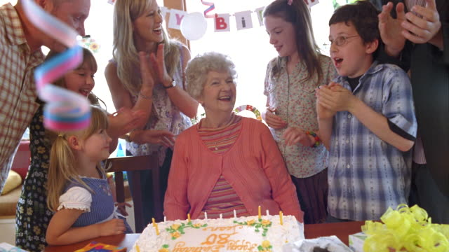 MS Senior woman blowing out candles on birthday cake with her family / Washington State, USA