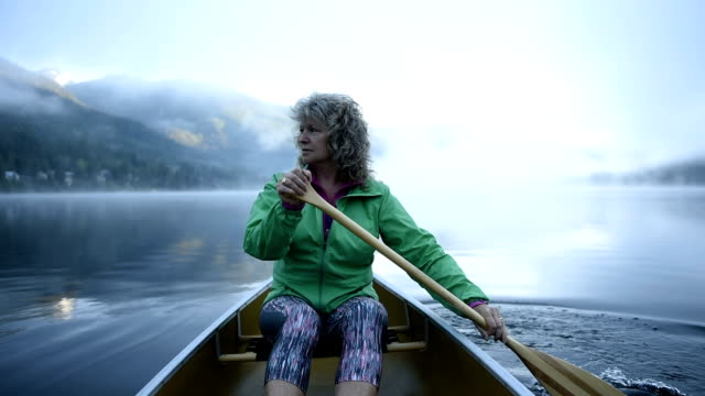 Senior Woman canoeing on a pristine lake