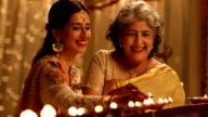 Senior woman celebrating diwali festival with her daughter, Delhi, India