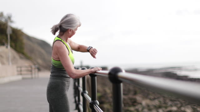 Senior woman checking an activity tracker on a run