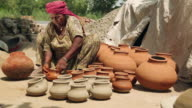 Senior woman colouring earthen pot, Haryana, India