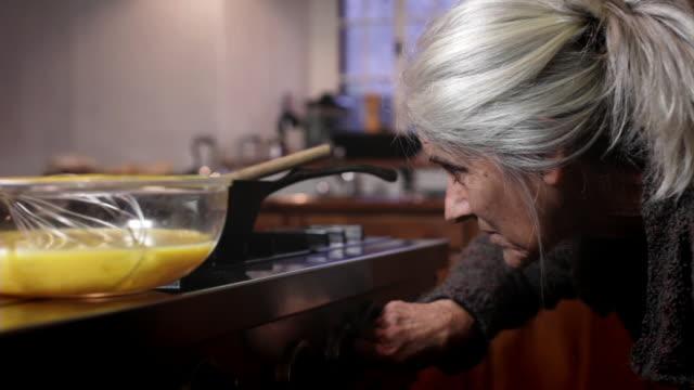 CU PAN Senior woman cooking in pan / Kingston, New York, USA