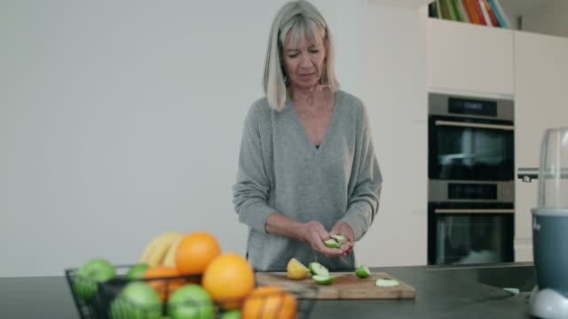 Senior woman cutting fruit for a smoothie