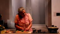 Senior woman cutting vegetables in kitchen, Delhi, India