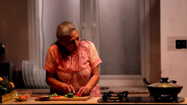 Senior woman cutting vegetables in kitchen, Delhi, India