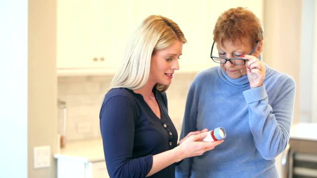 Senior woman, daughter discussing prescription medicine