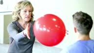 Senior woman doing physical therapy, tossing medicine ball