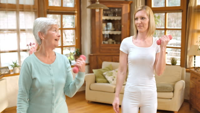 LD Senior woman doing weight exercises with nurse supervision