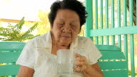 Senior woman drinking water in home
