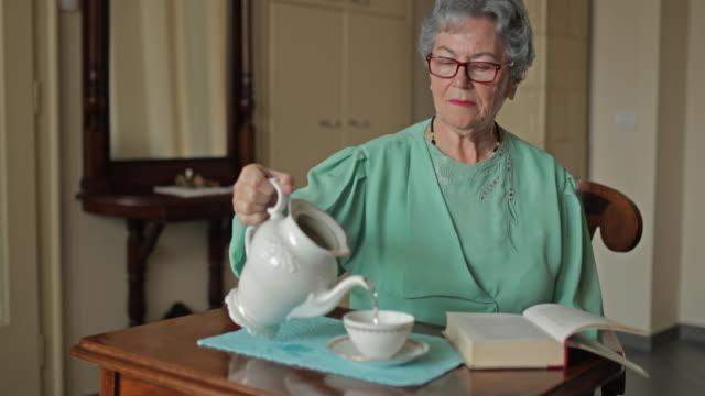 Senior woman enjoying in afternoon tea at home and looking at the camera.