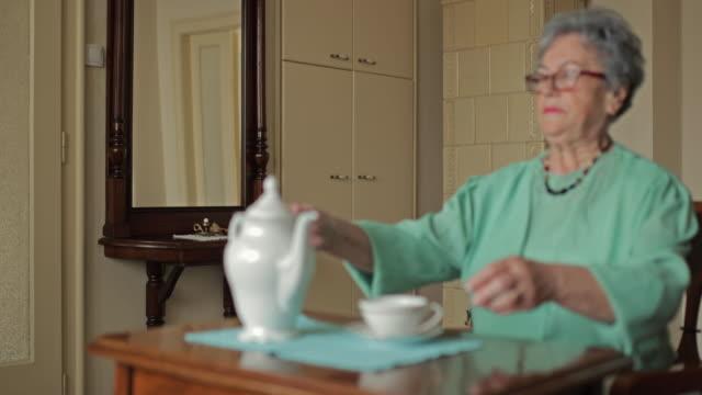 Senior woman enjoying in tea time at home and looking at camera.