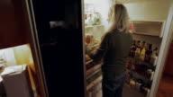MS ZO PAN Senior woman getting something out of refrigerator, man in background / Kingston, New York, USA