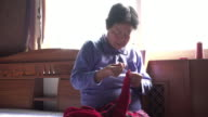 A senior woman hand sewing old sweater