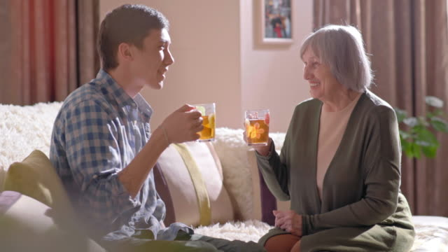 Senior woman having tea and chatting with young man