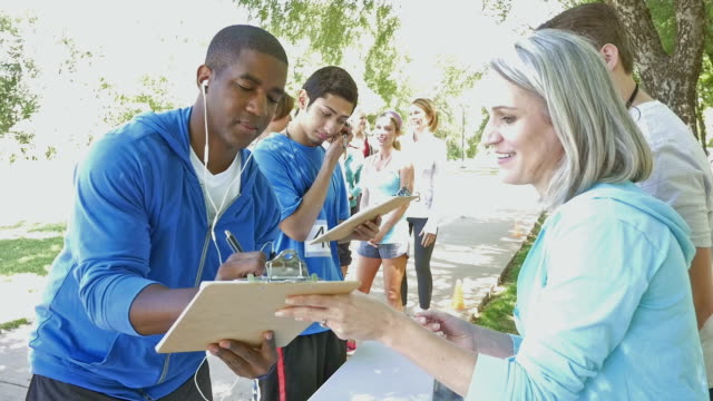 Senior woman helping marathon participants register for charity race