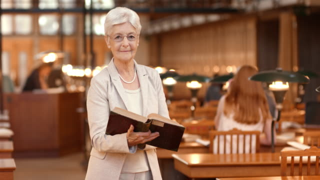 DS Senior woman holding a book standing in reading room