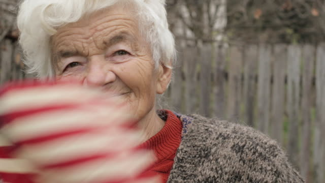 Donna anziana con bandiera americana guardando fotocamera e sorridente