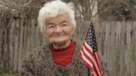 Senior Frau mit amerikanischer Flagge Blick in die Kamera und lächelnd