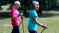 Senior woman holding hiking poles while walking with man