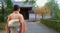 Senior vrouw in een Kimono wandelen door herfst tuinen