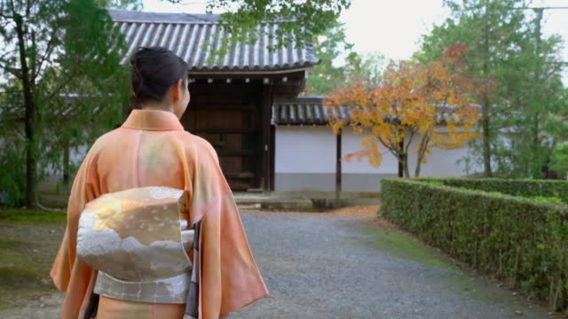 Senior woman in a Kimono walking through autumnal gardens