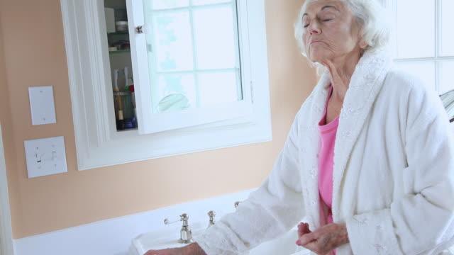 MS Senior woman in bathroom taking pills / Portland, Oregon, USA