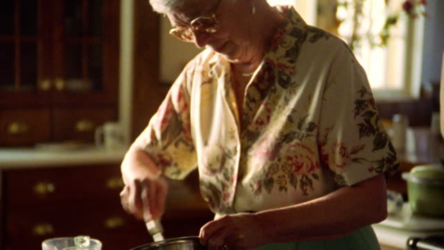 MS senior woman in eyeglasses stirring mixture in metal bowl in kitchen