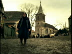 PORTRAIT senior woman in native dress standing / church + goats in background / Transylvania / FLASH FRAMES