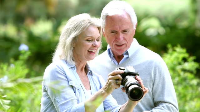 Senior woman in park taking photos, shows husband