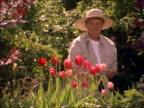 PORTRAIT senior woman in straw hat standing in garden